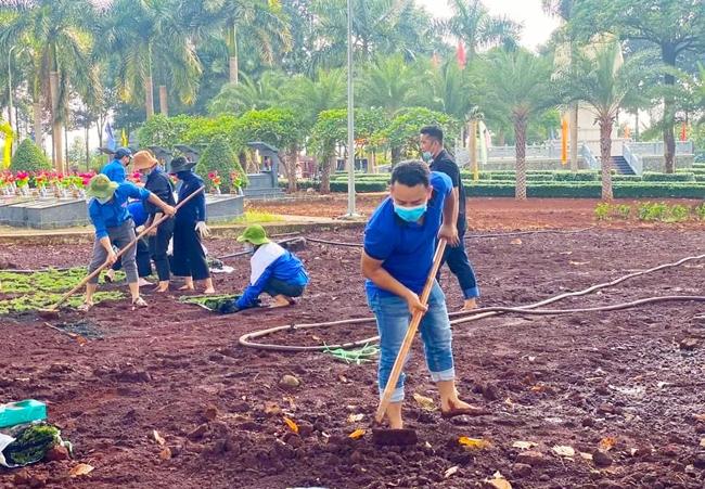 Thanh niên thị xã Phước Long góp ngày công lao động để trồng cỏ, chỉnh trang và tô điểm thêm vẻ đẹp của Nghĩa trang liệt sĩ thị xã