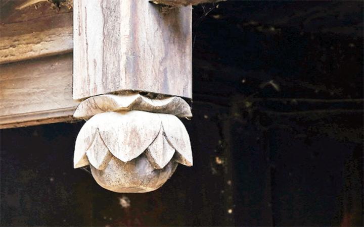 Đầu cột gỗ được trang trí hình hoa anh túc
