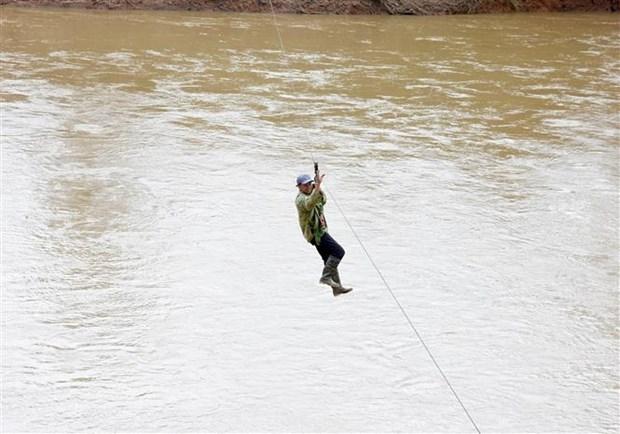Người dân liều mình đu dây qua sông Pô Kô. (Ảnh: Khoa Chương/TTXVN)