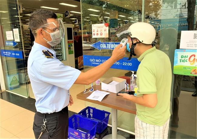Ngoài kiểm tra phiếu, tất cả người dân vào chợ, siêu thị đều được đo thân nhiệt