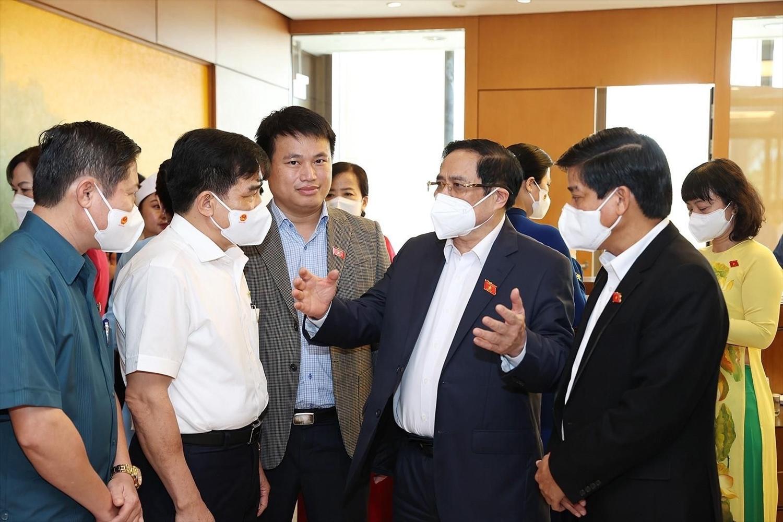 Thủ tướng Chính phủ Phạm Minh Chính trò chuyện với các đại biểu bên hành lang Quốc hội