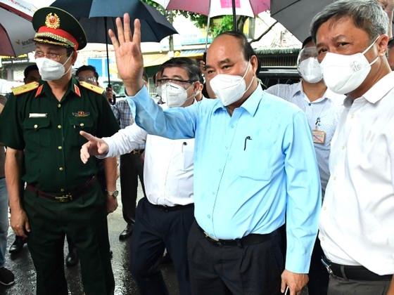 Chủ tịch nước Nguyễn Xuân Phúc thăm hỏi người dân khu vực phong tỏa ở huyện Hóc Môn. Ảnh: Báo SGGP