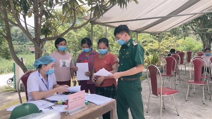 Cán bộ Đồn Biên phòng Thị Hoa và cán bộ y tế hướng dẫn các thủ tục cho người dân khi tiêm vaccine. Ảnh: Đức Linh