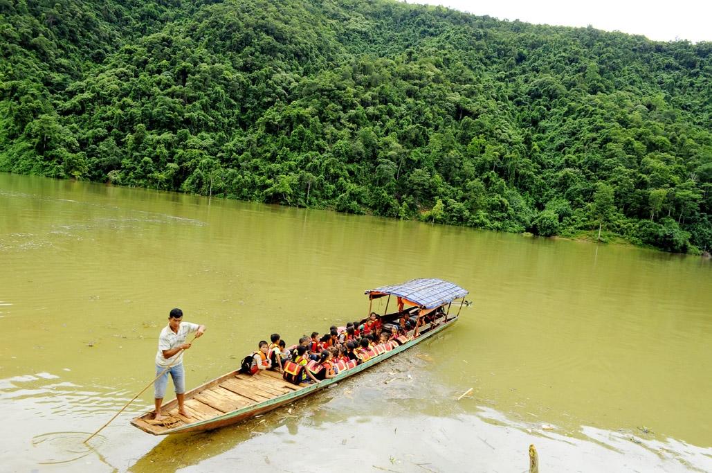 Ông San lái đò đưa các em học sinh qua sông Nậm Mu. (Ảnh chụp trước ngày 27/4/2021)
