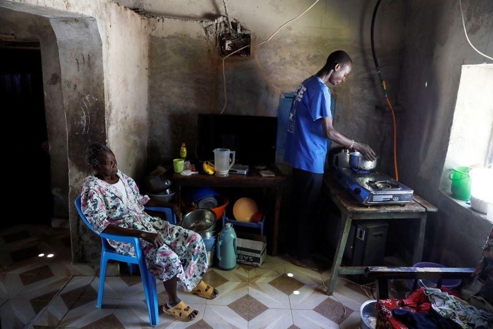 Anh Tony Otieno đang bật bếp đun bằng khí sinh học tại nhà bà nội ở gần thành phố Kisumu, Kenya. (Ảnh: Reuters).