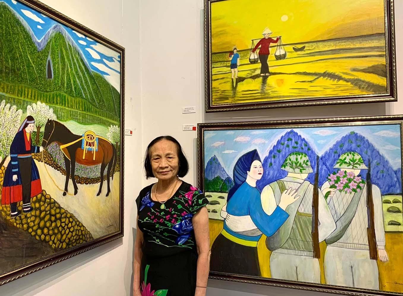 Bà giáo Nguyễn Ngọc Dậu bên các bức tranh của mình