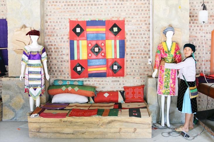 Sùng Thị Si giới thiệu sản phẩm trang phục truyền thống của dân tộc Mông do HTX Lanh Trắng làm ra. Ảnh: Thanh Thuận