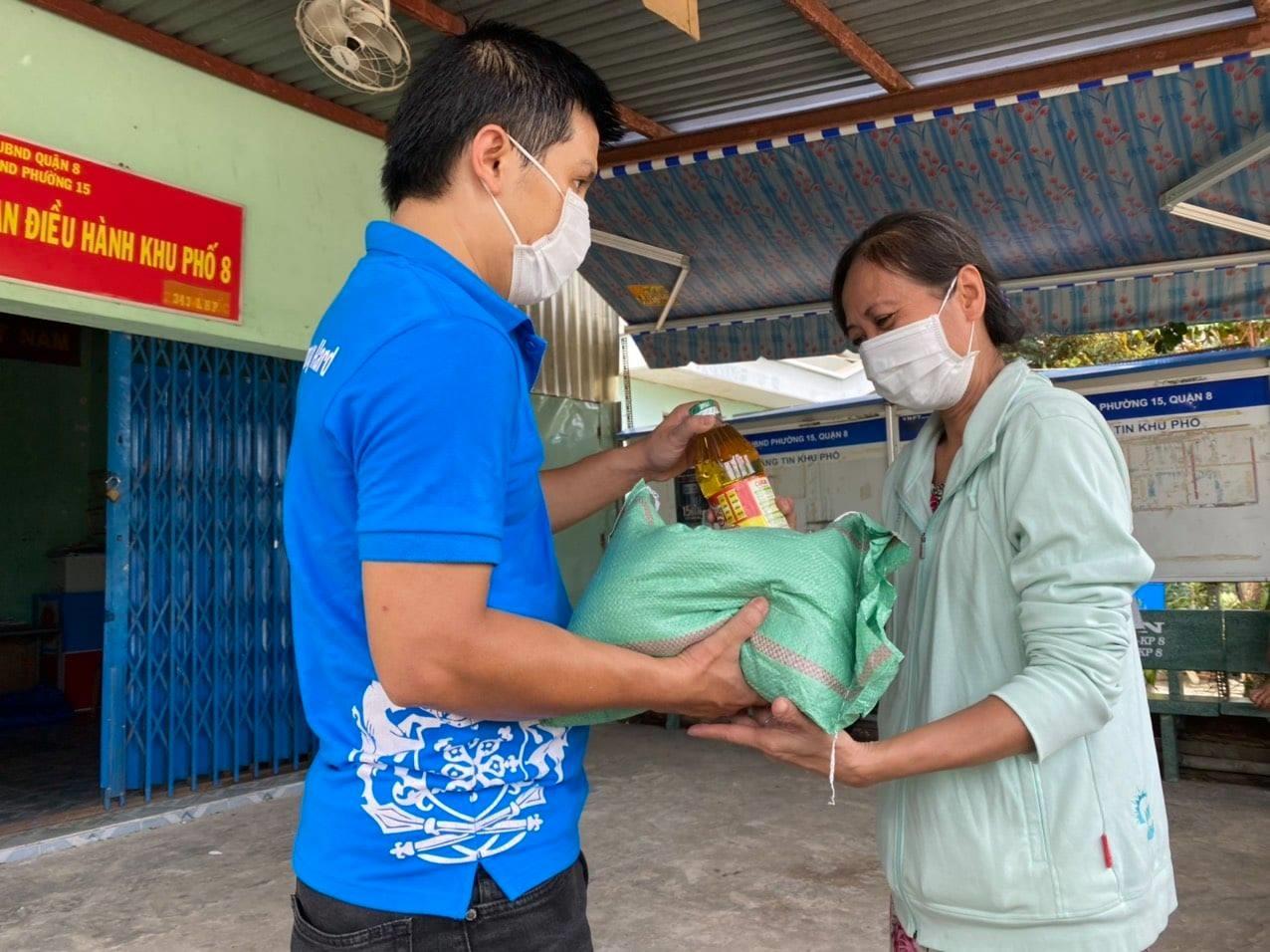 Anh Tiêu Minh Hải và nhóm từ thiện đang tặng gạo và thực phẩm cho bà con khó khăn
