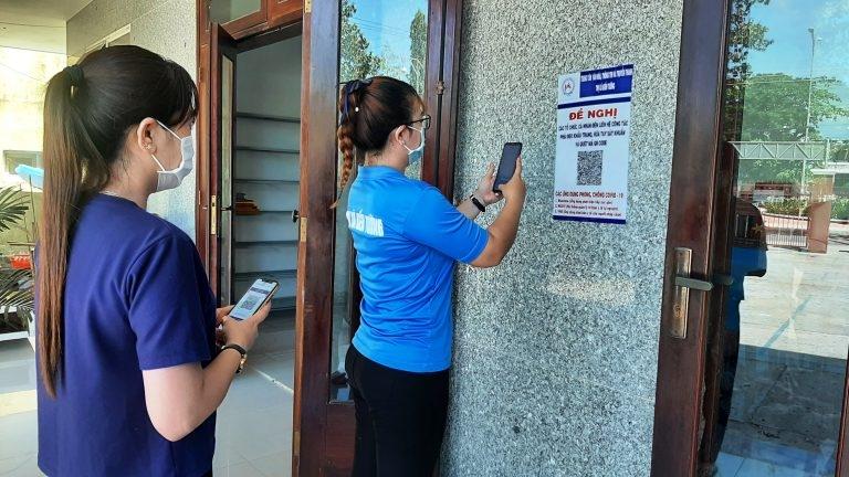 Người dân tới làm việc thực hiện việc quét mã QR để khai báo y tế. Ảnh minh họa
