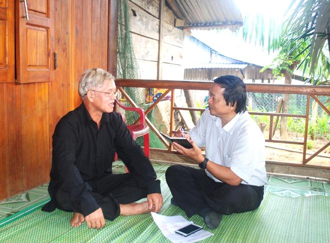 Ông Zơrâm Nhiêl (bên trái) chia sẻ với tác giả về công việc của Người có uy tín, cũng như sự đổi thay cuộc sống của bà con Cơ Tu thôn Pà Rum hiện nay