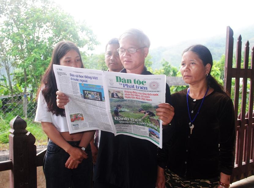 Ông Zơrâm Nhiêl đọc báo tuyên truyền về những chủ trương của Đảng, chính sách, pháp luật của Nhà nước cho bà con Cơ Tu trong thôn