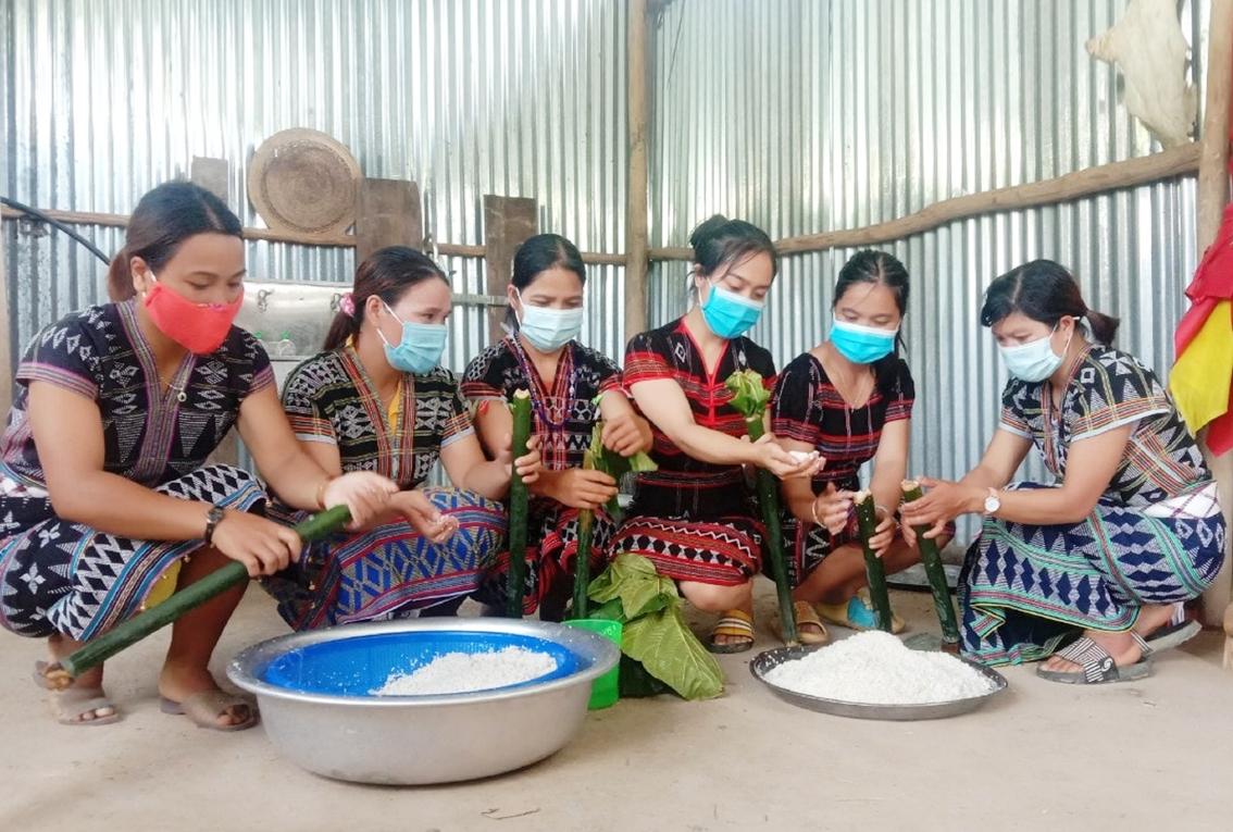 Những bàn tay mềm mại của chị em phụ nữ đưa gạo vào ống nứa để nướng cơm lam gửi về xuôi