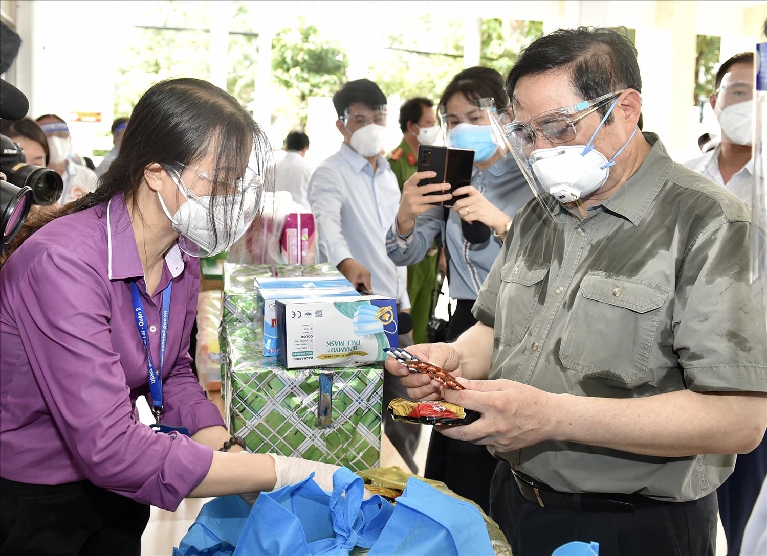Thủ tướng xem các loại nhu yếu phẩm, thuốc men... trong túi an sinh sẽ được cung cấp cho người dân. Ảnh: VGP/Nhật Bắc