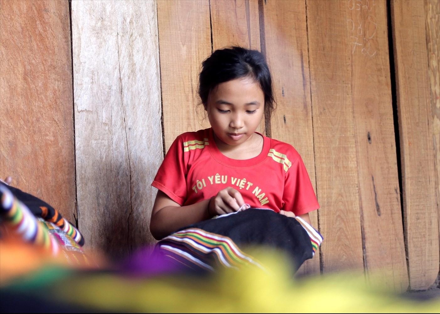 Chưa đầy 10 tuổi nhưng cô bé Lương Thị Lệ Quyên, ở bản Đàng, xã Nga My, huyện Tương Dương đã biết thêu hoa văn lên chân váy rất thuần thục
