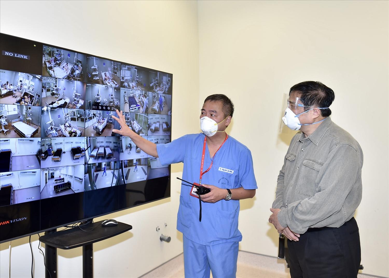 Bác sĩ Nguyễn Lân Hiếu, Giám đốc Bệnh viện Đại học Y Hà Nội phụ trách Bệnh viện dã chiến điều trị COVID-19 tại Bệnh viện quốc tế Becamex giới thiệu với Thủ tướng hoạt động điều trị chung của Bệnh viện dã chiến qua hệ thống giám sát trung tâm. Ảnh: VGP/Nhật Bắc
