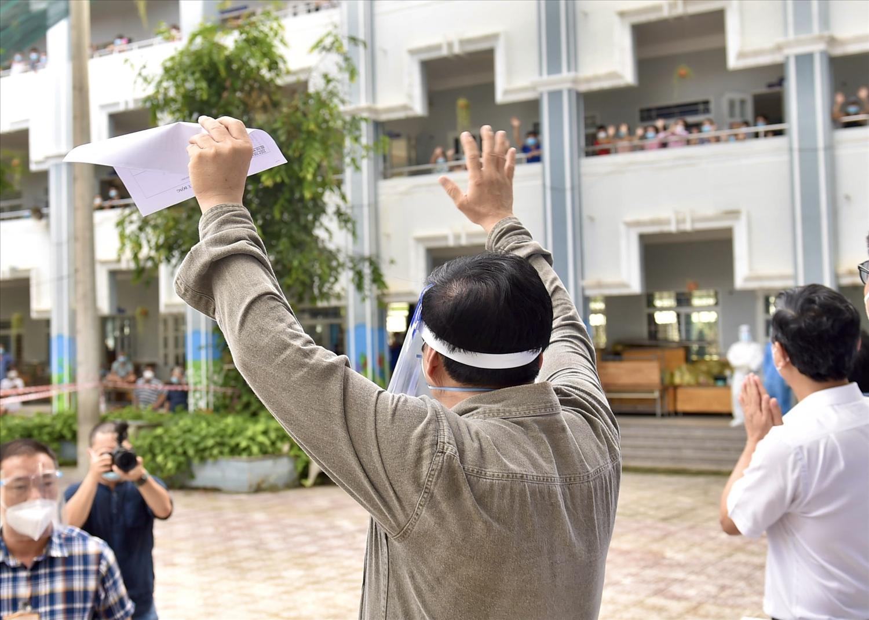 Thủ tướng vẫy chào, động viên bà con đang thực hiện cách ly tập trung tại Trường Tiểu học Bình Thuận, phường Thuận Giao, TP. Thuận An. Ảnh: VGP/Nhật Bắc