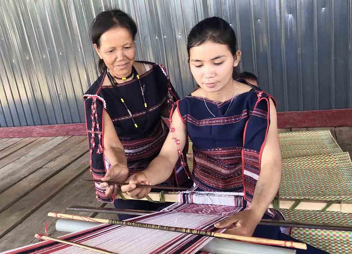 Bà Đinh Thị Drinh ở tổ dân phố Plei Nghe (thị trấn Kông Chro) truyền dạy nghề dệt thổ cẩm cho thế hệ trẻ (ảnh chụp trước ngày 27/4/2021)