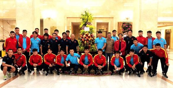 Đội tuyển Việt Nam chụp ảnh với lẵng hoa của Chủ tịch nước Nguyễn Xuân Phúc ngay khi đặt chân đến khách sạn Grand Plaza - Ảnh: VFF
