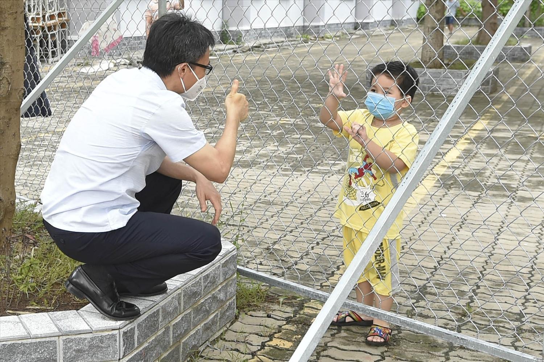 Phó Thủ tướng Vũ Đức Đam hỏi chuyện với một cháu bé nhiễm COVID-19 tại khu cách ly Phước Kiển. Ảnh: VGP/Đình Nam