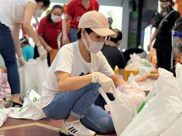 Ca sỹ Uyên Linh đóng gói nhu yếu phẩm để trao cho người dân gặp khó khăn do COVID-19. (Nguồn: tuoitre.vn)
