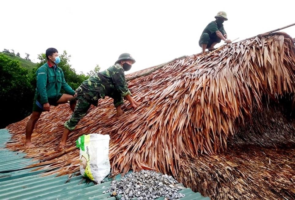 Chiến sỹ Đồn Biên phòng Ra Mai (Bộ đội Biên phòng Quảng Bình) hỗ trợ đồng bào Chứt ở xã Thượng Hóa, huyện Tuyên Hóa (Quảng Bình) chằng chống nhà cửa