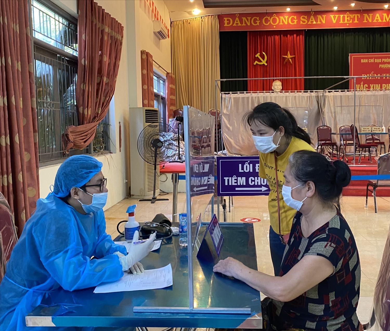 Bà Nguyễn Thị Vương có tiền sử mắc bệnh nền được các nhân viên y tế tư vấn các thủ tục trước khi tiêm tại Nhà Văn hóa phường Dịch Vọng, quận Cầu Giấy