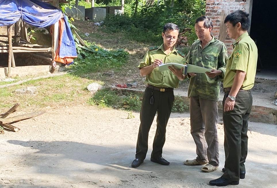 Cán bộ kiểm lâm Trạm Kiểm lâm Minh Quang tuyên truyền gia đình anh Dư Văn Tám ở thôn Quang Minh, xã Minh Quang không xây dựng nhà, cơi nới chuồng trại trong khu vực rừng đặc dụng. (Ảnh chụp trước ngày 27/4/2021)