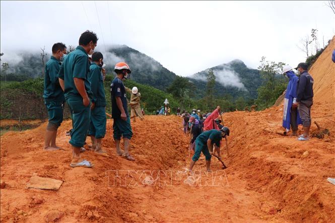 Lực lượng đoàn viên, thanh niên, dân quân tự vệ và người dân xã Trà Thuỷ, huyện Trà Bồng dọn dẹp hàng nghìn mét khối đất, đá bị sạt lở tại con đường độc đạo dẫn vào thôn 1 và thôn 4. Ảnh: Sỹ Thắng/TXVN
