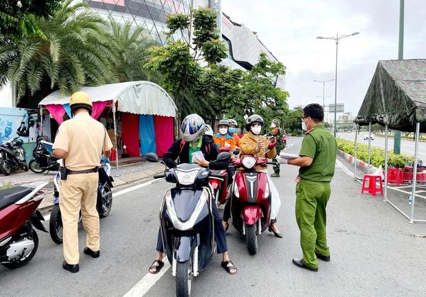Lực lượng Công an tại chốt kiểm tra trên đường Phạm Văn Đồng (phường Hiệp Bình Chánh, Thủ Đức) kiểm tra giấy tờ của người lưu thông. Ảnh: TTXVN