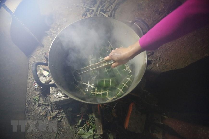 Sau khi gói xong, xếp bánh vào nồi, lót lá dong xuống đáy và trên cùng để không bị cháy và giữ được hơi. Bánh được luộc trong khoảng 12-15 giờ, sau khi luộc xong, rửa bánh trong nước lạnh cho sạch nhựa, để ráo hoặc túm lại treo lên. (Ảnh: Trọng Đạt/TTXVN)