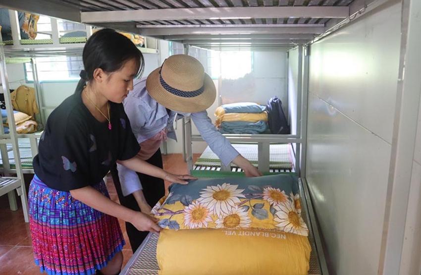 Giáo viên Trường PTDTBT THCS xã Nậm Ban hướng dẫn học sinh bán trú gấp chăn, màn