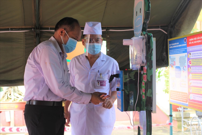 """Thiếu tá Lê Mạnh Hùng (bên phải) đang hướng dẫn người dân cách sử dụng """"Rô bốt rửa tay sát khuẩn"""""""