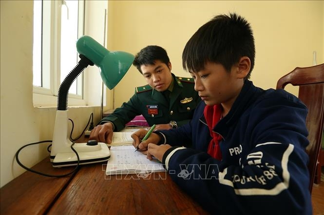 Chiến sỹ đồn Biên phòng Pa Thơm, tỉnh Điện Biên hướng dẫn cháu Quàng Trung Thành học bài sau giờ lên lớp. Ảnh: Phan Tuấn Anh/TTXVN
