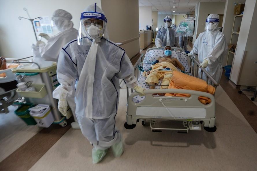 Tình nguyện viên N.A.D (người đi sau cùng) hỗ trợ y bác sĩ sắp xếp chỗ nằm cho F0 tại khu B, Trung tâm Nhiệt đới Bệnh viên Hữu nghị Đa khoa Nghệ An