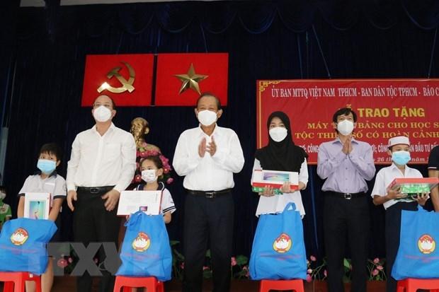Ông Trương Hòa Bình, nguyên Ủy viên Bộ Chính trị, nguyên Phó Thủ tướng Thường trực Chính phủ, Chủ tịch Danh dự Quỹ Bảo trợ học sinh dân tộc thiểu số, học sinh nghèo Báo Công an Nhân dân (giữa), ông Nguyễn Hồ Hải, Phó Bí thư Thành ủy Thành phố Hồ Chí Minh (thứ 2 từ trái sang) trao tặng máy tính bảng cho các học sinh dân tộc Chăm và Khmer