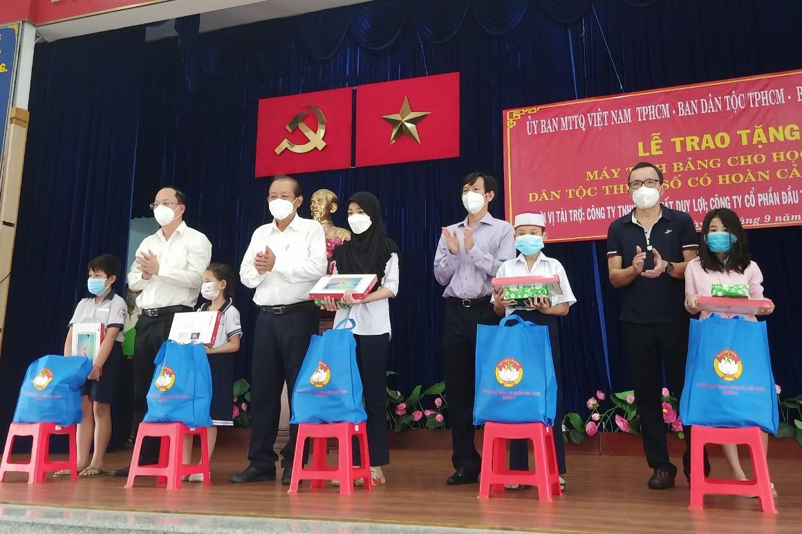 Ông Trương Hòa Bình cùng đại diện lãnh đạo TP. Hồ Chí Minh và đơn vị tài trợ trao máy tính bảng và quà cho đại diện các em học sinh DTTS khó khăn trên địa bàn