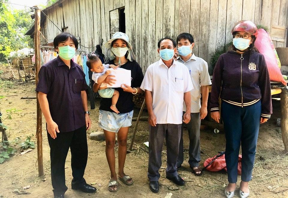 Ông La Văn Nghĩa (mặc áo trắng, đứng giữa) trao quà hỗ trợ của UBDT cho gia đình chị KPá Hờ Nghiệp