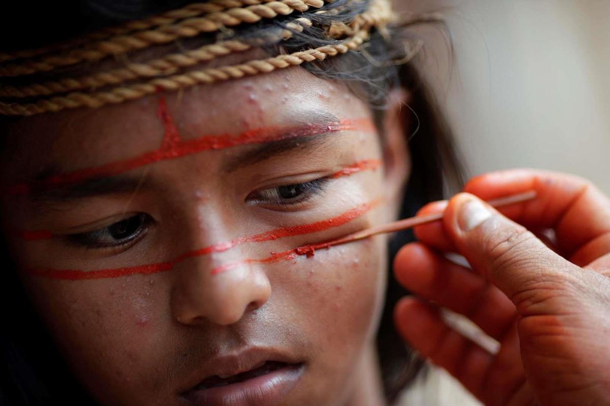 Các thành viên bộ lạc thổ dân Mura dùng sơn đỏ cam để hóa trang theo phong tục để gửi đến truyền thông quốc tế thông điệp bảo tồn rừng Amazon. Ảnh: Reuters.