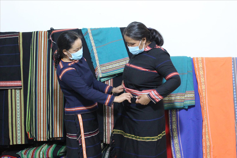 Chị Pel (bên trái) và chị Dui đang giới thiệu về về bộ váy áo truyền thống của người Gia Rai