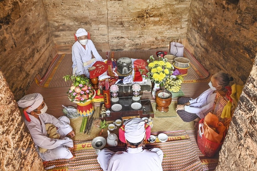 Thực hiện nghi lễ cúng tháp Pô Sah Inư. (Ảnh: Nguyễn Thanh/TTXVN)