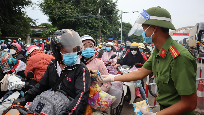 Người dân về quê qua địa bàn tỉnh Bình Phước được tặng bánh, sữa. Ảnh: HOÀNG GIÁP