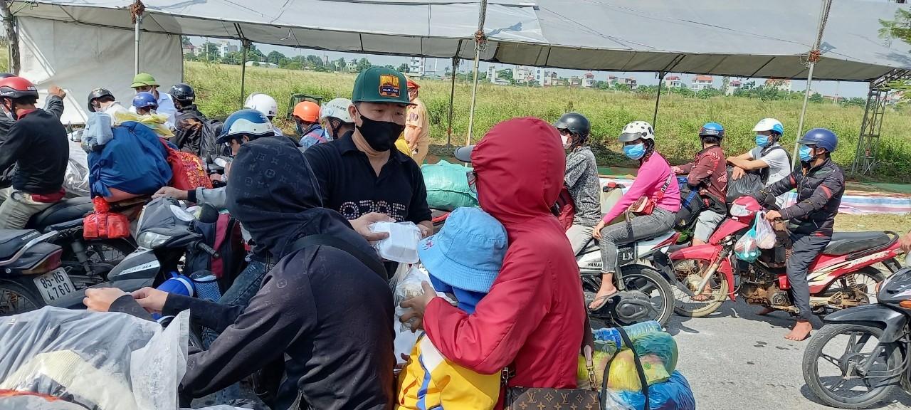 Anh Dương Thế Anh (khẩu trang đen) là thành viên của nhóm hoạt động thiện nguyện tặng đồ ăn dọc đường cho bà con