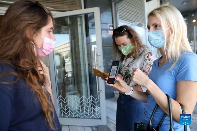 """Người dân Israel xuất trình """"thẻ xanh COVID-19"""" khi tới một nhà hàng ở thành phố Modiin, miền Trung Israel, ngày 7/10/2021. (Ảnh: Xinhua)"""