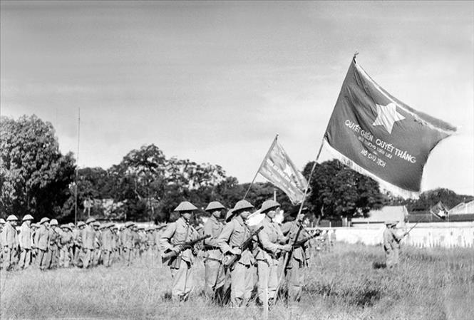 """Một đơn vị của Trung đoàn Thủ đô với lá cờ """"Quyết chiến, quyết thắng"""" của Chủ tịch Hồ Chí Minh tặng tham dự Lễ chào cờ đầu tiên trong Ngày giải phóng Thủ đô, diễn ra tại sân Cột Cờ (nay là Đoan Môn - Hoàng thành Thăng Long) vào lúc 15 giờ ngày 10/10/1954. Ảnh: Tư liệu TTXVN"""