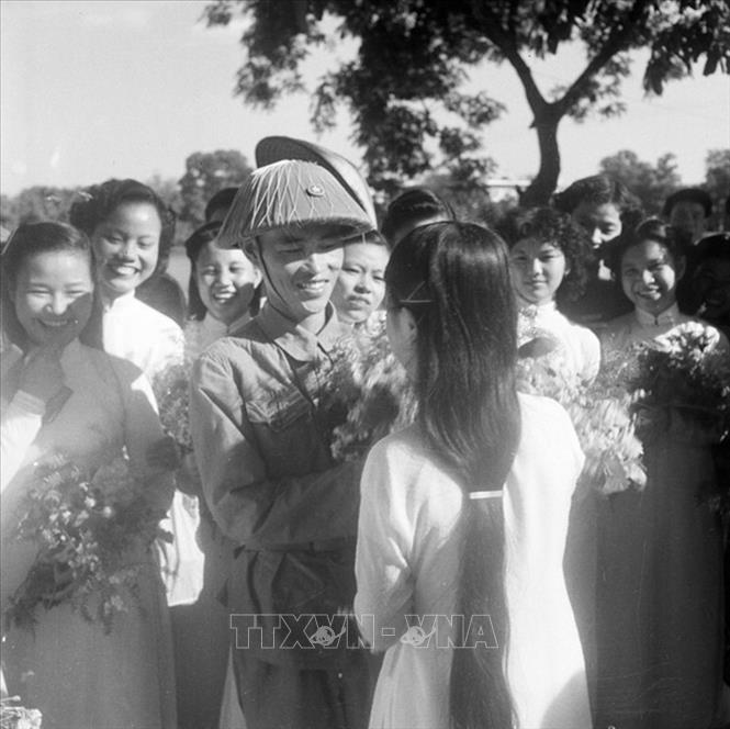 Thiếu tướng Vương Thừa Vũ, Tư lệnh Đại đoàn 308, Chủ tịch Ủy ban Quân chính Thành phố giữa vòng vây của các nữ sinh trường Trưng Vương tặng hoa chúc mừng bên hồ Hoàn Kiếm trong ngày giải phóng Thủ đô. Ảnh: Tư liệu TTXVN