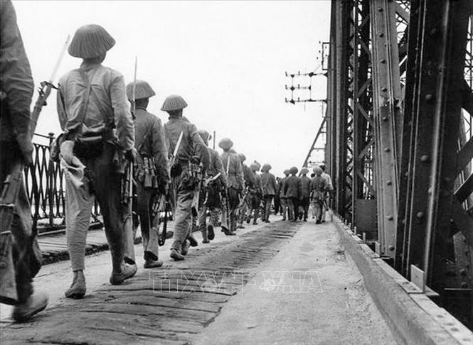 Bộ đội ta hùng dũng tiến qua cầu Long Biên vào tiếp quản Hà Nội, cùng lúc quân Pháp rút khỏi Hà Nội qua cây cầu này phía chiều bên kia, chiều 9/10/1954. Ảnh: Tư liệu TTXVN
