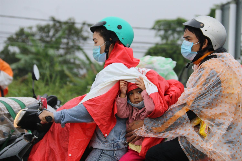 Nhiều gia đình mang theo con nhỏ chạy xe máy về quê